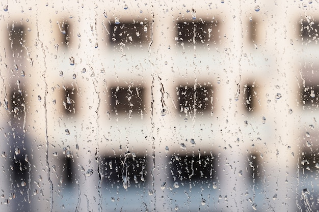 Gotas de água no vidro, gotas de chuva naturais na janela com fundo desfocado