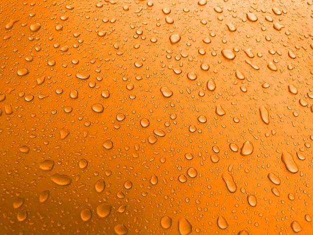 Gotas de água sobre uma superfície de metal laranja, fundo bonito depois da chuva