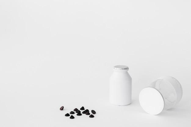 Gotas de chocolate perto de garrafa e jarra de produtos lácteos