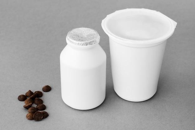 Gotas de chocolate perto de recipientes com produtos lácteos
