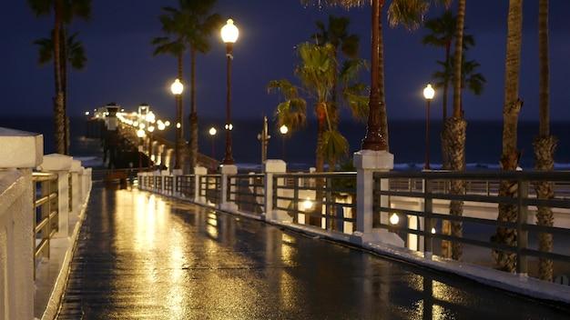 Gotas de chuva ao anoitecer em oceanside, califórnia, eua. cais, palmeiras no crepúsculo do crepúsculo. reflexo de luz.