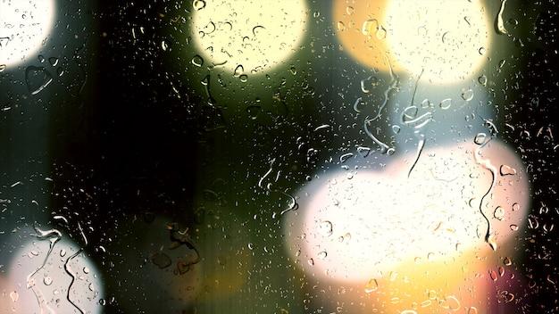 Gotas de chuva caem no vidro contra o fundo de bokeh de carros em movimento