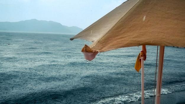 Gotas de chuva caindo do guarda-sol molhado na praia do mar.