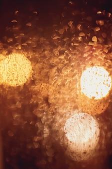 Gotas de chuva e luzes borradas através de uma janela.