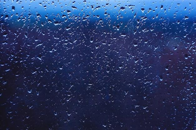 Gotas de chuva na janela. água no copo. gotas em execução. plano de fundo conceitual.