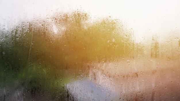 Gotas de chuva na janela com luz de sinalização