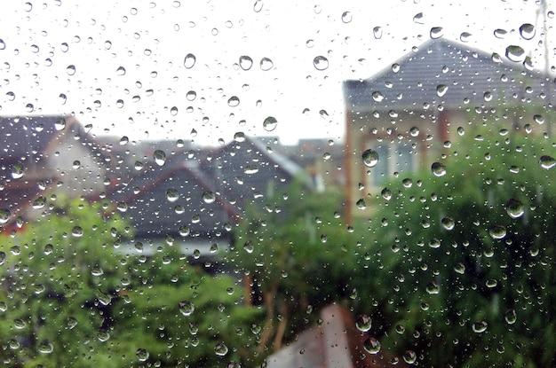 Gotas de chuva na janela de vidro com fundo borrado de moradores e árvores