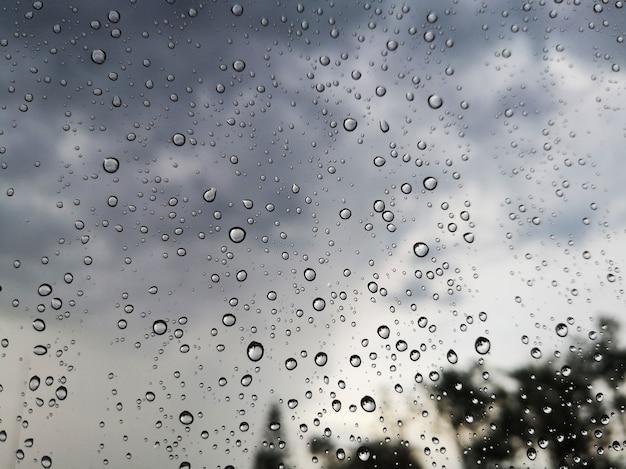 Gotas de chuva na janela de vidro transparente com fundo escuro da nuvem