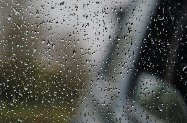 Gotas de chuva na superfície dos vidros da janela com fundo nublado.