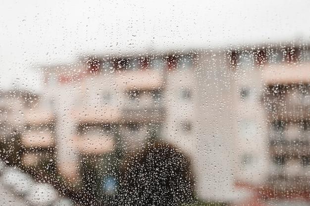 Gotas de chuva na vidraça de uma janela com formas borradas de prédios, cidade grande. gotas de chuva no vidro da janela. foco seletivo.
