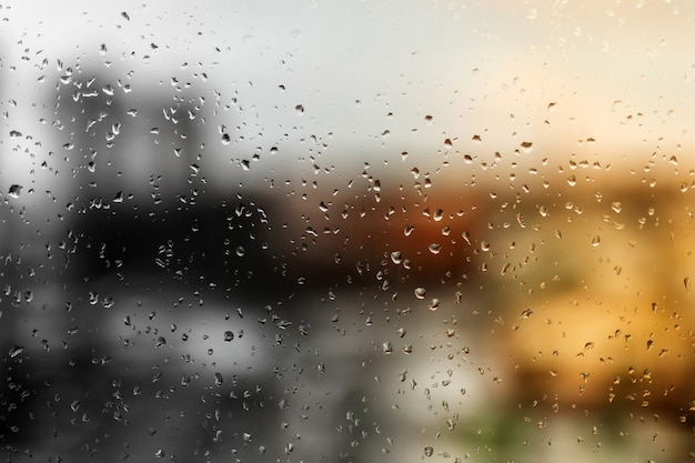 Gotas de chuva na vidraça de uma janela, edifícios de rua ao fundo.