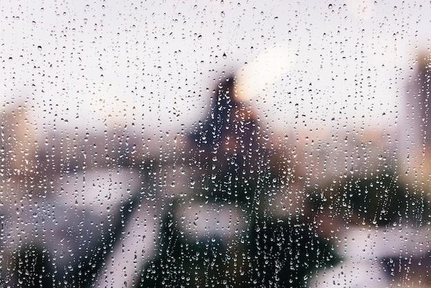 Gotas de chuva nas janelas de vidro na hora de ouro com edifícios altos do borrão ao fundo.
