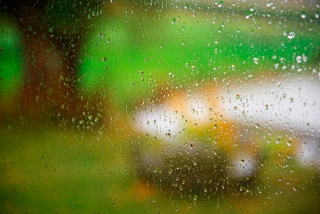 Gotas de chuva no fundo de vidro da janela durante o outono