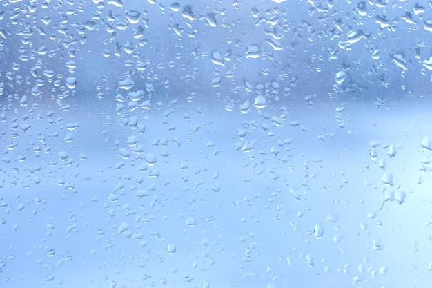 Gotas de chuva no vidro da janela azul limpo