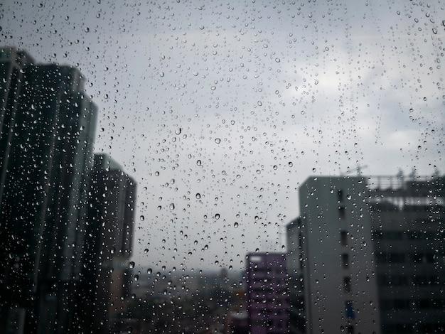 Gotas de chuva no vidro da janela com edifício turva do arranha-céu na cidade.