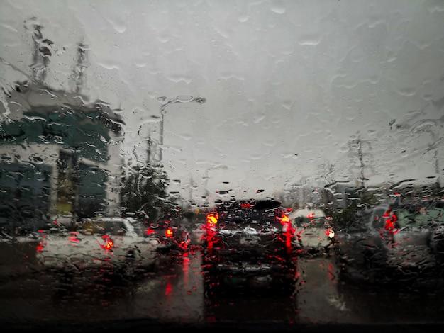 Gotas de chuva no vidro da janela do carro com fundo desfocado.