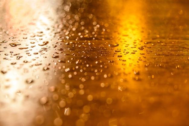 Gotas de chuva sobre uma mesa de madeira iluminada por postes de luz uma noite.