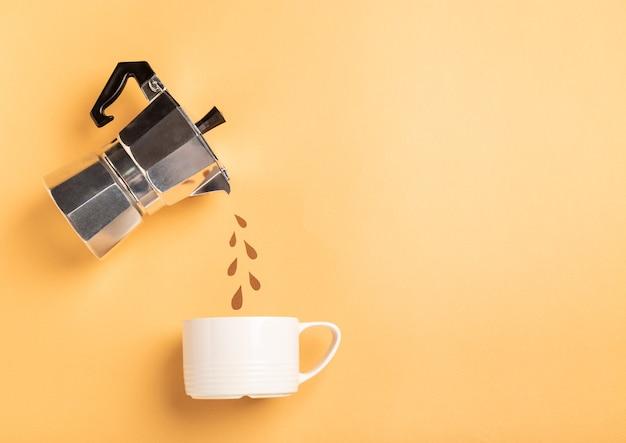Gotas de corte de papel derramando de uma cafeteira gêiser em um copo sobre fundo de papel amarelo. conceito de preparação de café. vista superior, configuração plana. design minimalista. espaço para texto.