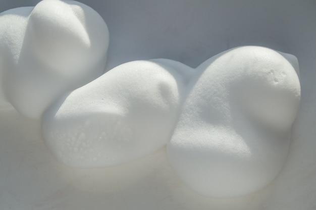 Gotas de espuma de barbear, mousse ou espuma de cabelo estilo sobre fundo branco