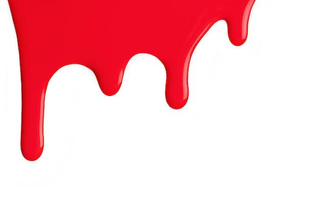 Gotas de líquido vermelho brilhante da cor da tinta fluem para baixo no fundo branco isolado