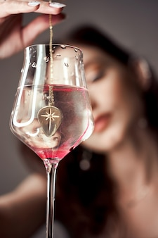 Gotas de sangue vermelho pintam em um copo d'água, uma mulher olha para o copo.