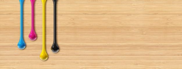 Gotas de tinta 3d cmyk isoladas em fundo bege de madeira. banner horizontal. ilustração