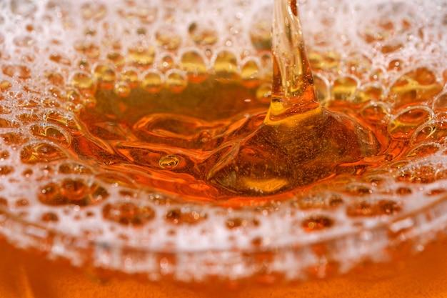 Gotas e bolhas de cerveja light em um tiro de bala de vidro macro fotografia