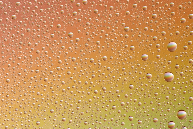 Gotas em vidro de diferentes tamanhos e cores em um fundo colorido, textura