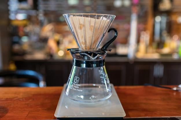 Gotejamento de café com caneca de vidro e filtro de papel no balcão