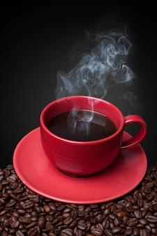 Gotejamento de café xícara vermelha closeup e feijão de café fresco no preto