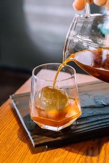 Gotejamento frio jarra de café preto com vidro e gelo em cafeteria e restaurante