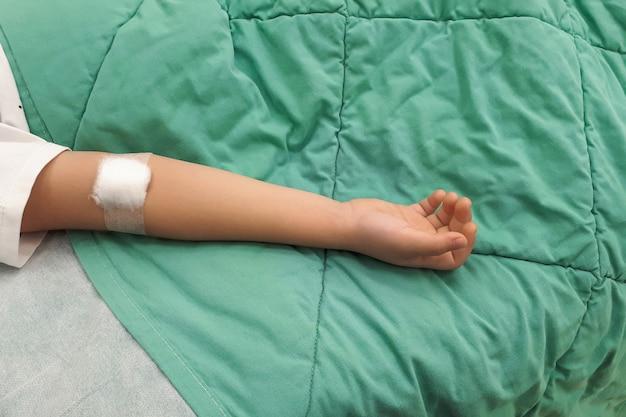 Gotejamento iv na mão criança em uma cama de hospital
