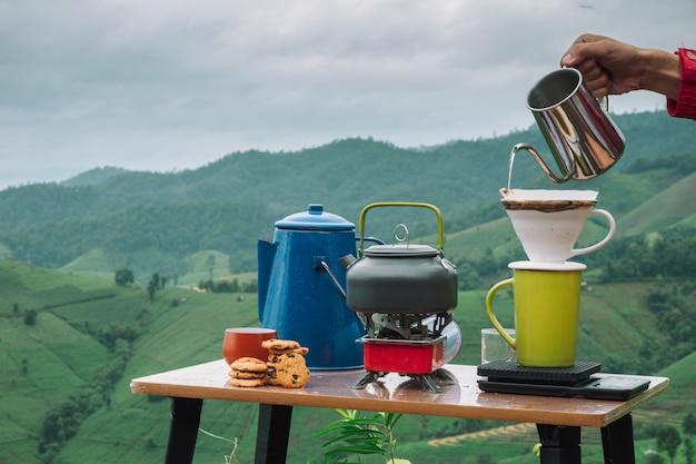 Goteje café com filtro de manhã na vista para a montanha