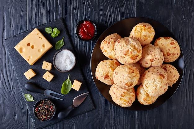 Gougeres, bolinhos de queijo em uma placa preta. pãezinhos de choux de queijo francês tradicional. ingredientes e molho de tomate em uma mesa de madeira preta, vista de cima, flatlay