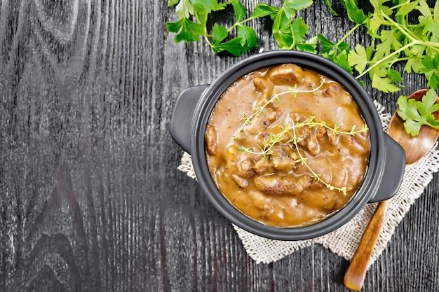 Goulash de carne em molho de tomate com raminhos de tomilho em uma panela sobre serapilheira, colher, salsa na placa de madeira preta de cima