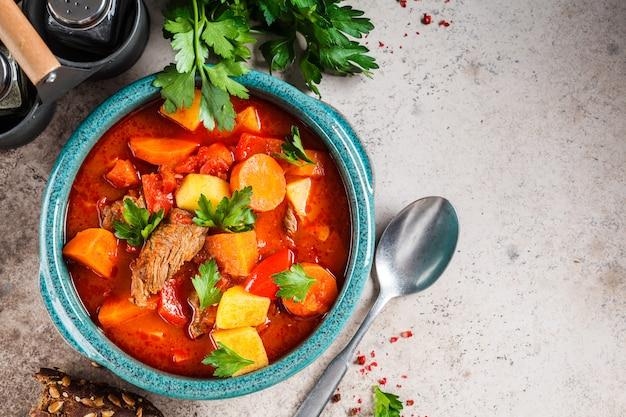 Goulash húngaro tradicional. guisado de carne com batatas, cenouras e paprika no prato azul, vista superior, espaço da cópia.