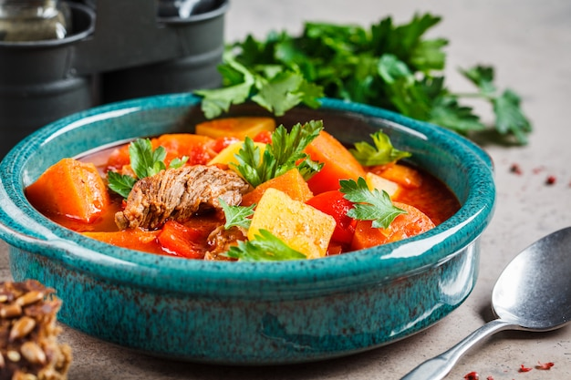 Goulash húngaro tradicional. guisado de carne com batatas, cenouras e pimentão no prato azul.