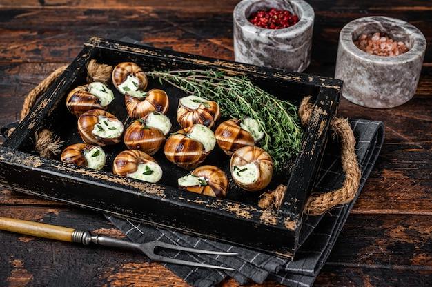 Gourmet francês - escargot caracóis com manteiga de alho em uma bandeja de madeira. fundo de madeira. vista do topo.