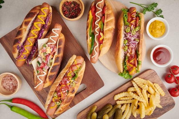 Gourmet grelhados todo cachorro-quente de carne com acompanhamentos e batatas fritas. deliciosos e simples cachorros-quentes com mostarda, pimenta, cebola e nachos. cachorro-quente totalmente carregado com coberturas variadas em uma prancha de remo.