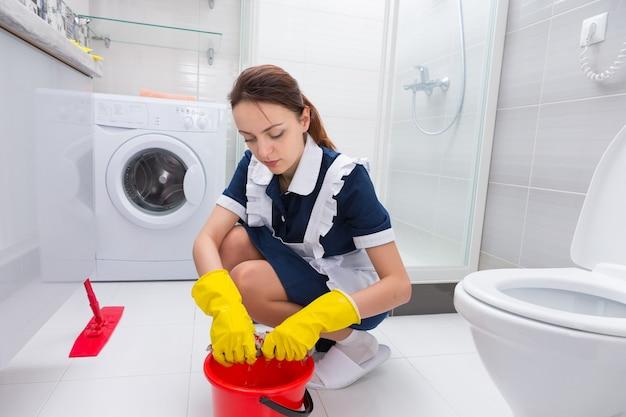 Governanta ajoelhada em seu uniforme limpando o chão de um banheiro com um esfregão e um balde torcendo um pano com as mãos enluvadas