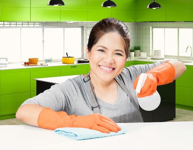 Governanta asiática limpando a mesa com o fundo da cozinha