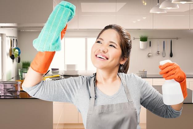Governanta asiática limpando vidro com fundo de cozinha