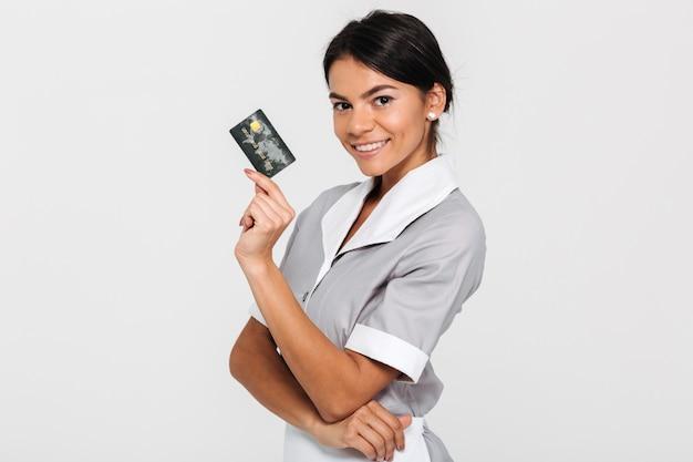 Governanta atraente jovem de uniforme cinza, segurando o cartão de crédito
