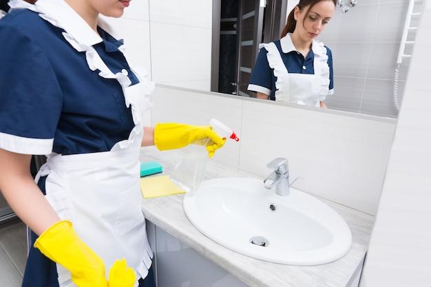 Governanta borrifando um lavatório em um banheiro branco e limpo com detergente de um frasco de aerossol, enquanto ela faz a manutenção de uma casa ou suíte de hotel