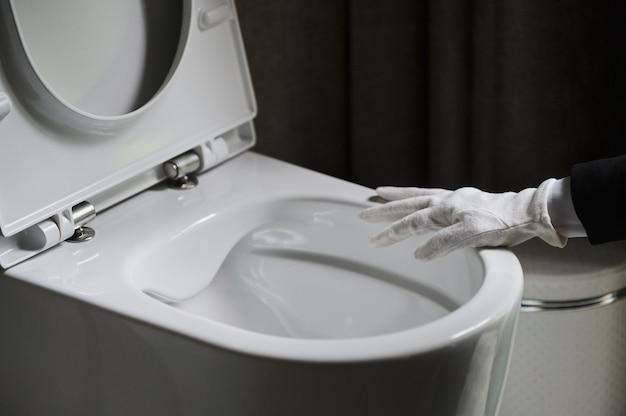 Governanta em um avental branco elegante em pé, esfregando um vaso sanitário com uma escova