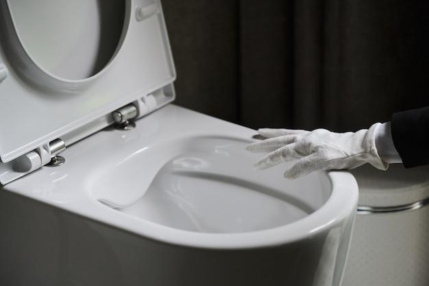 Governanta em um avental branco limpo, esfregando um vaso sanitário com uma escova.