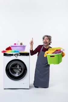 Governanta exultante, vista frontal, ajoelhando-se perto da máquina de lavar, segurando o cesto de roupa suja no fundo branco