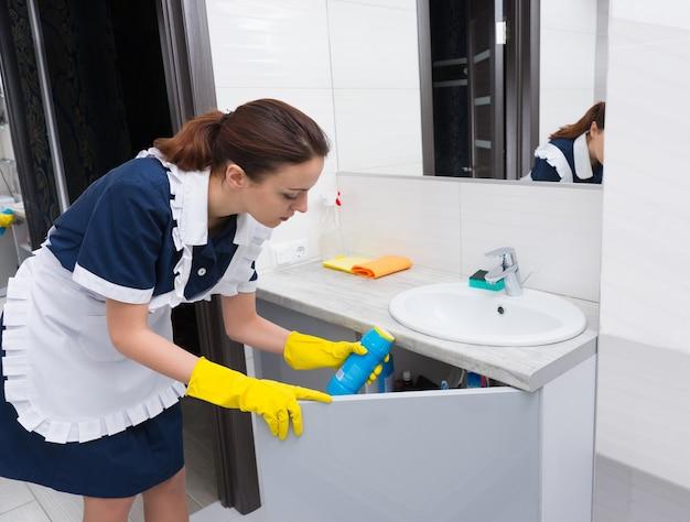 Governanta feminina com avental branco sobre vestido azul retirando um frasco de limpador de debaixo do armário da pia no banheiro