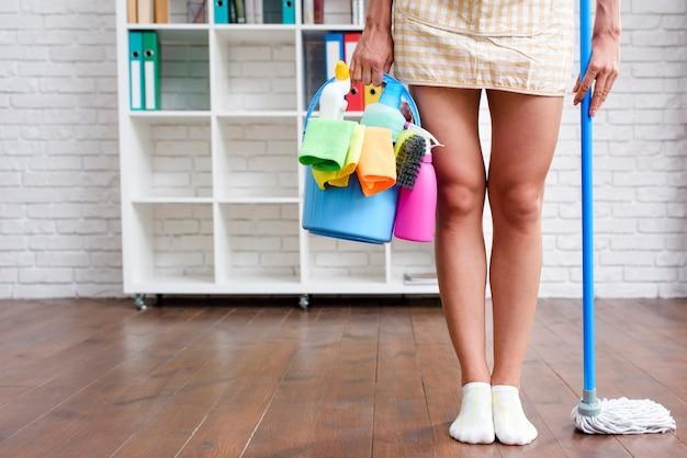 Governanta feminina em pé em casa com produto de limpeza e esfregão