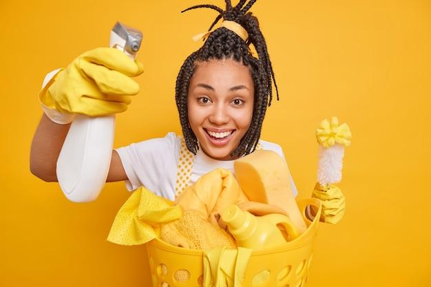 Governanta feminina positiva usa luvas protetoras de borracha, faz a rotina de limpeza doméstica segura a escova e o detergente coleta a roupa suja isolada sobre o fundo amarelo. limpeza do dia de limpeza